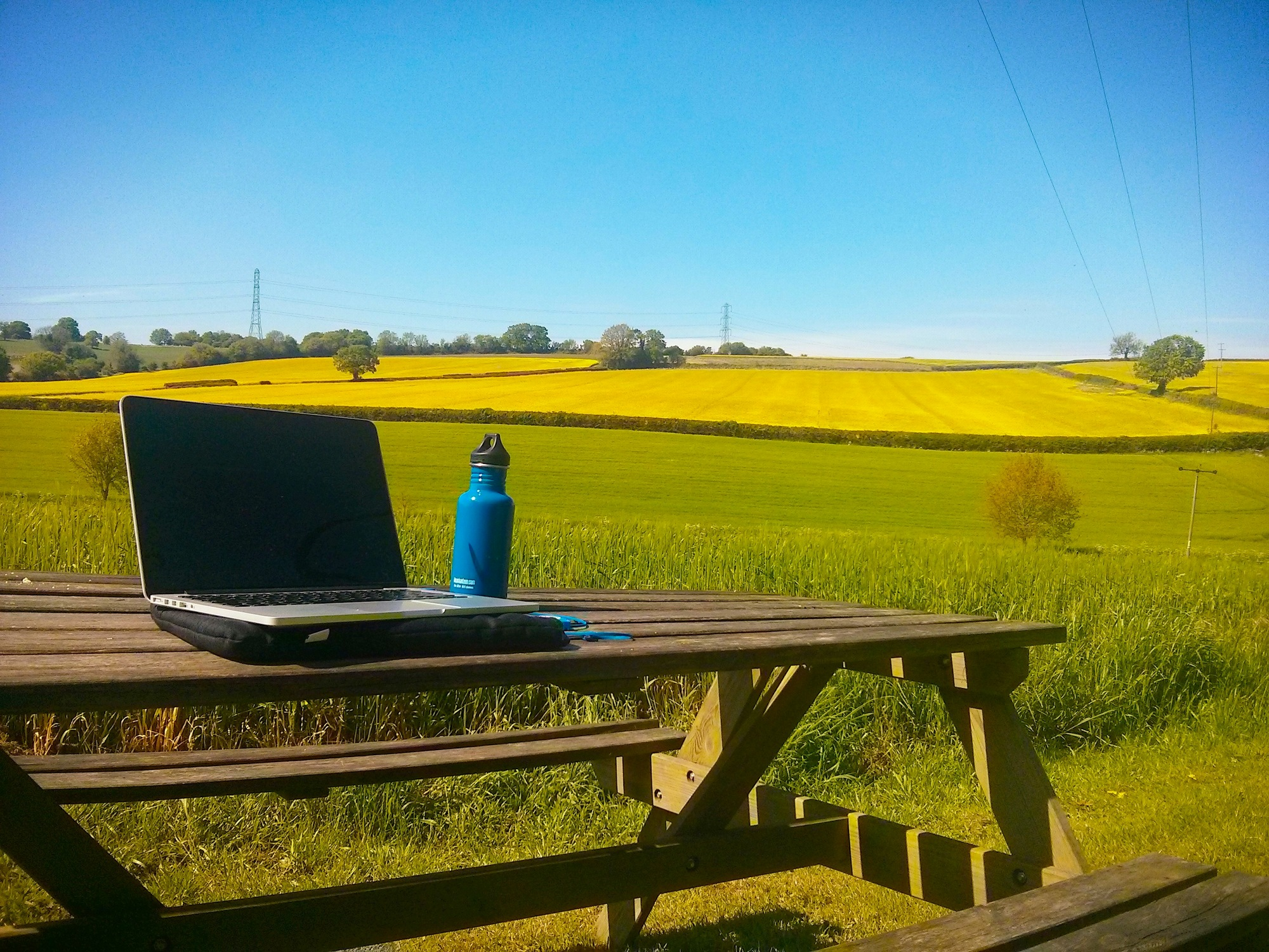 View across green and yellow fields with blue sky. A laptop sits on a table in the foreground.