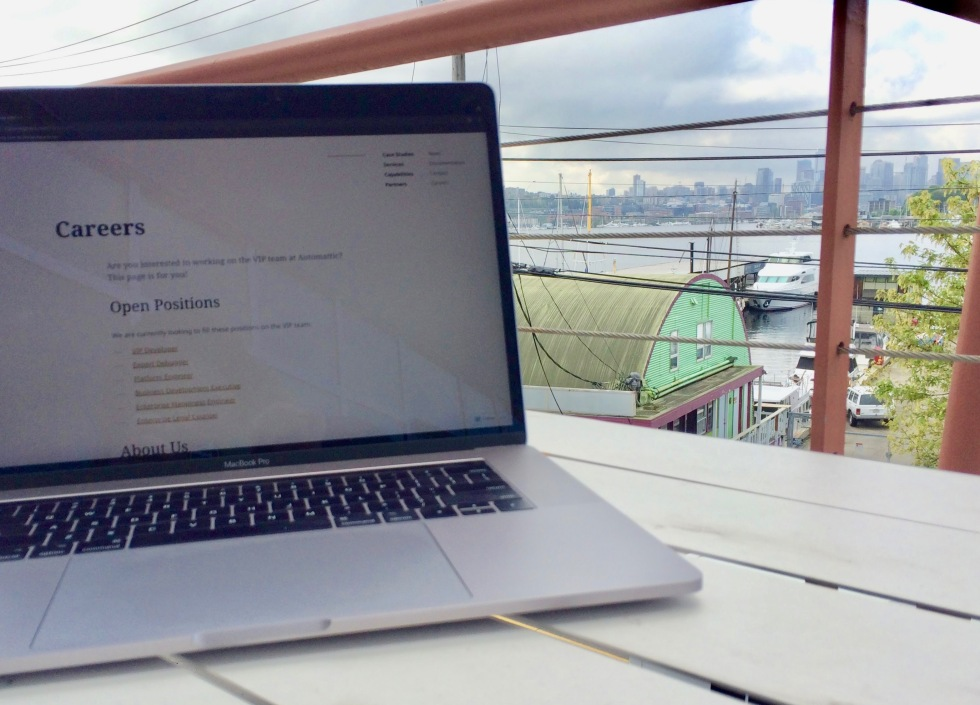 Laptop on table with Seattle skyline and Lake Union in the background