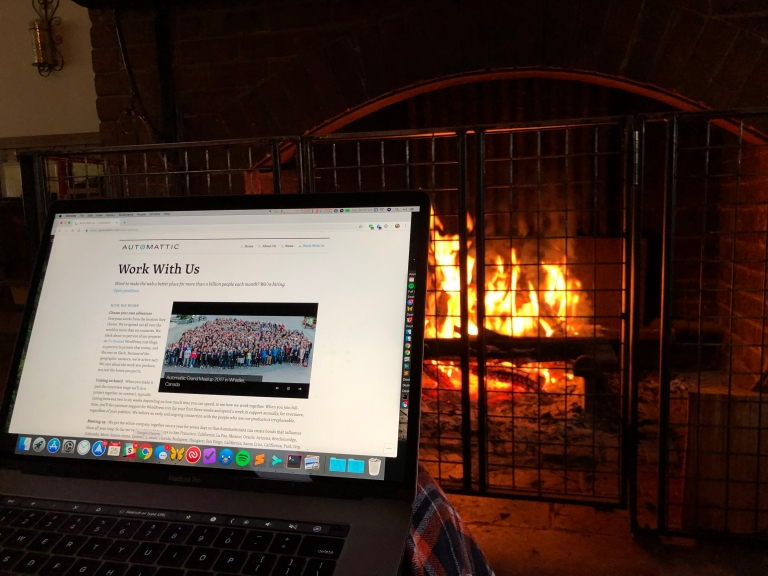 A laptop in front of a cosy fireplace. The laptop has Automattic's Work With Us page on it.