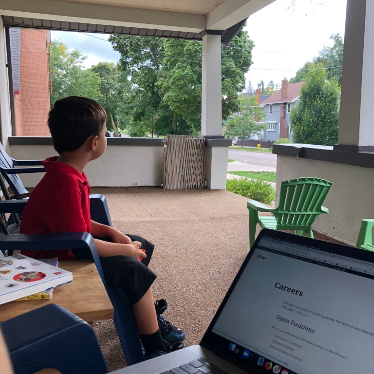 child sitting on front porch, next to open laptop